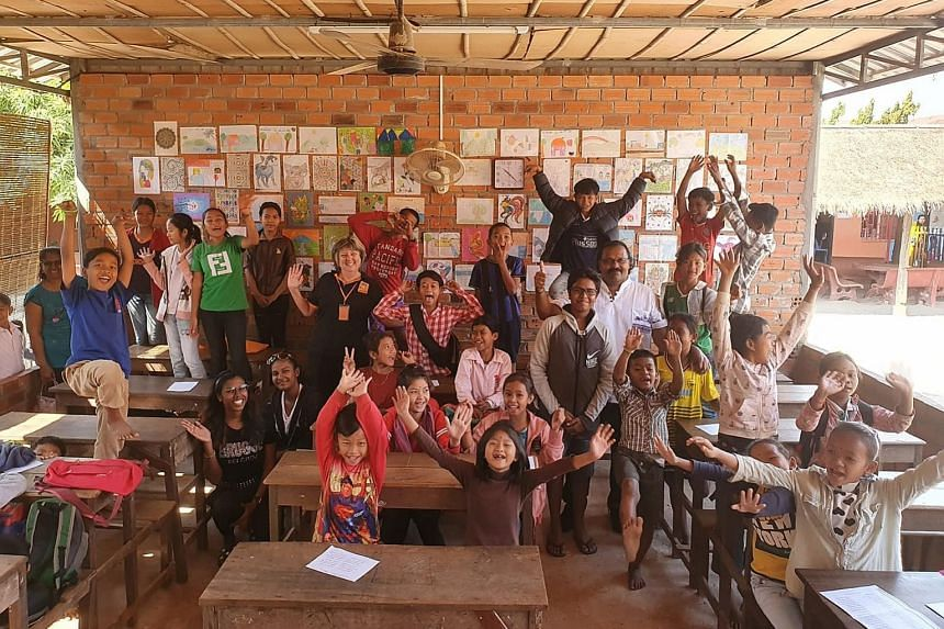 Mr Kevin Raja (in white shirt) and his family with the children and staff of a community school run by non-profit charity Feeding Dreams Cambodia in Siem Reap last month.
