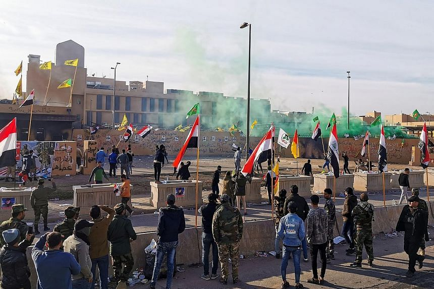 Protesters and militia fighters gathered outside the US Embassy in Baghdad yesterday to condemn air strikes on bases belonging to Iraq's pro-Iranian force Hashed al-Shaabi. US troops guarding the embassy fired tear gas as the protesters set US flags