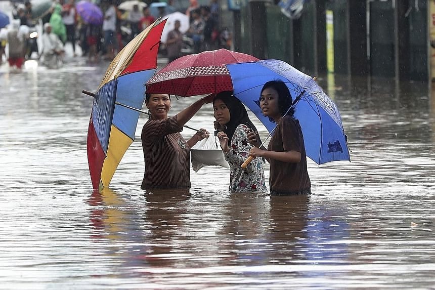People wading through floodwaters in Jatibening, on the outskirts of Jakarta, yesterday. Electricity was cut off in many of the city's neighbourhoods, with some train lines and an airport also shut.