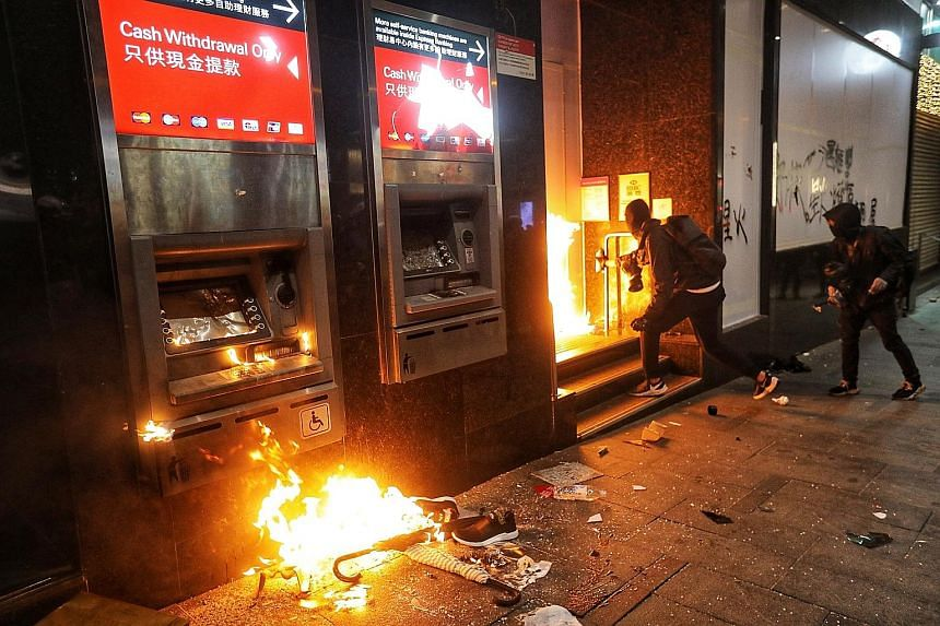 Protesters setting fire to automated teller machines outside a bank during the anti-government rally in Hong Kong yesterday. PHOTO: EPA-EFE Protesters marching in Hong Kong during a massive pro-democracy rally on New Year's Day, looking to carry the