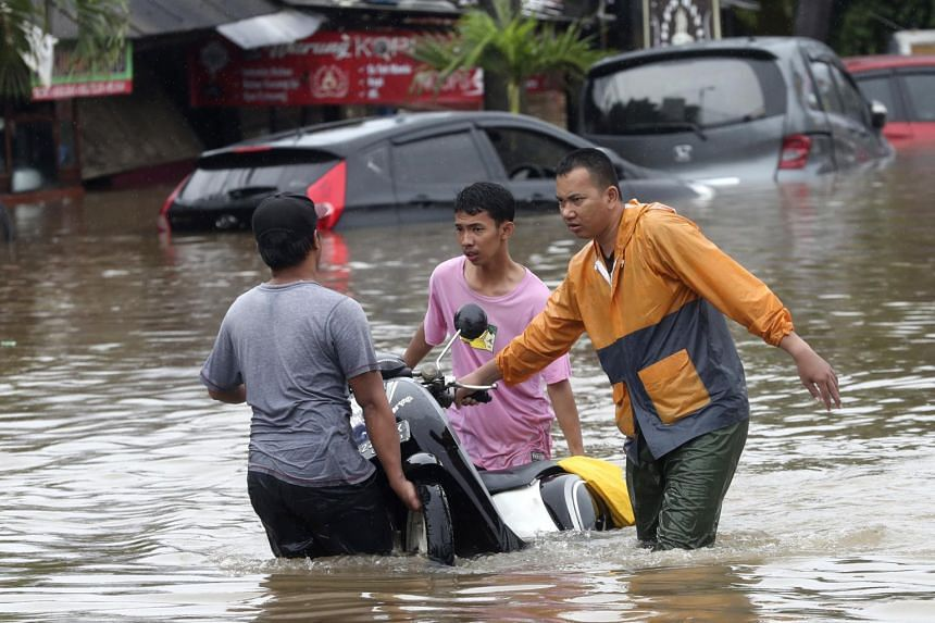 Residents wading through floodwaters at Jatibening on the outskirts of Jakarta, on Jan 1, 2020.