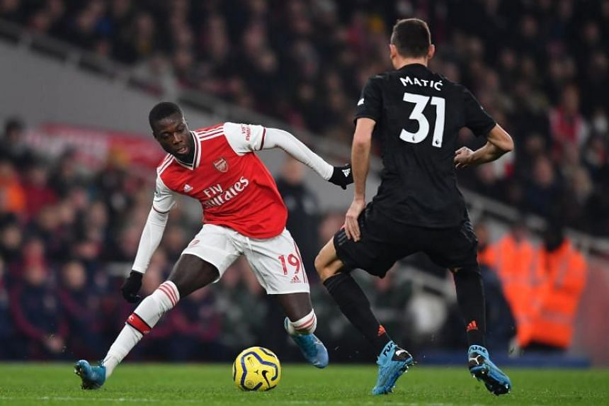 Arsenal midfielder Nicolas Pepe (left) vies with Manchester United midfielder Nemanja Matic during the English Premier League football match in London on Jan 1, 2020.