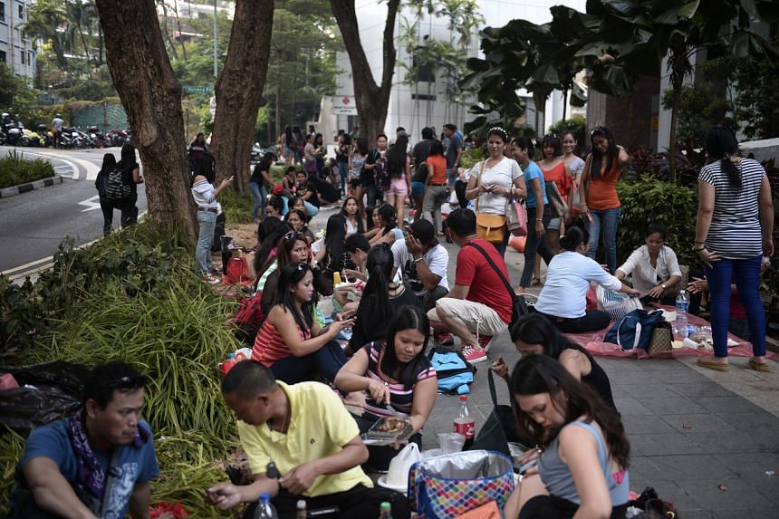 Groups of people gather for picnics at a pavement near Tong Building.