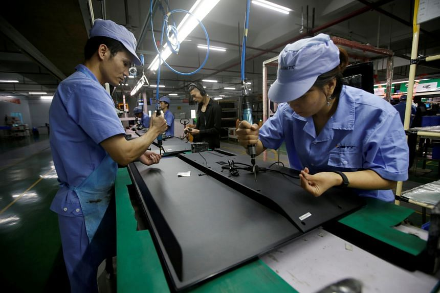 Employees working on a production line of a television factory in Shenzhen, China, on Aug 8, 2019.