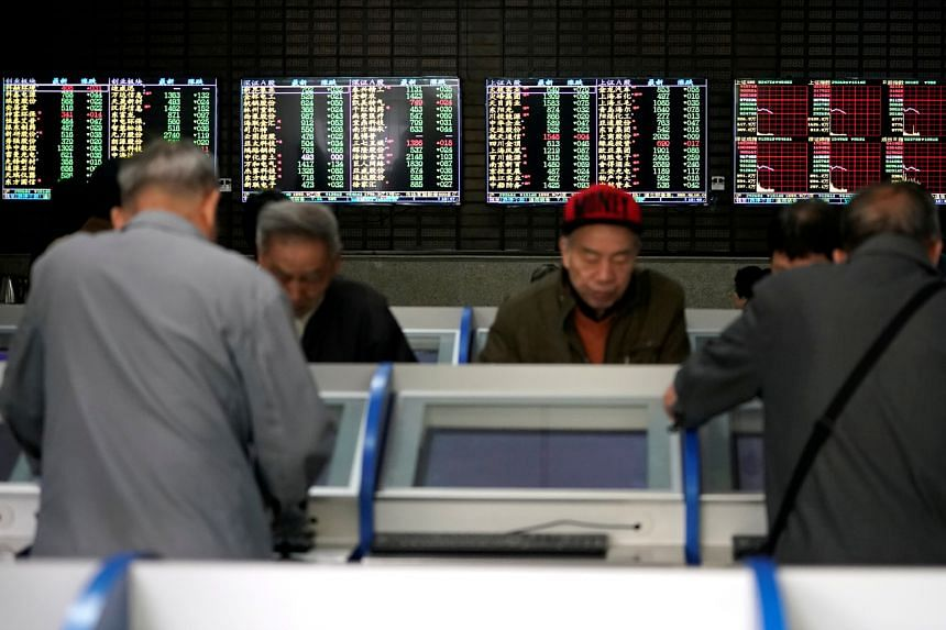 In a photo from May 6, 2019, investors look at computer screens showing stock information at a brokerage house in Shanghai, China.
