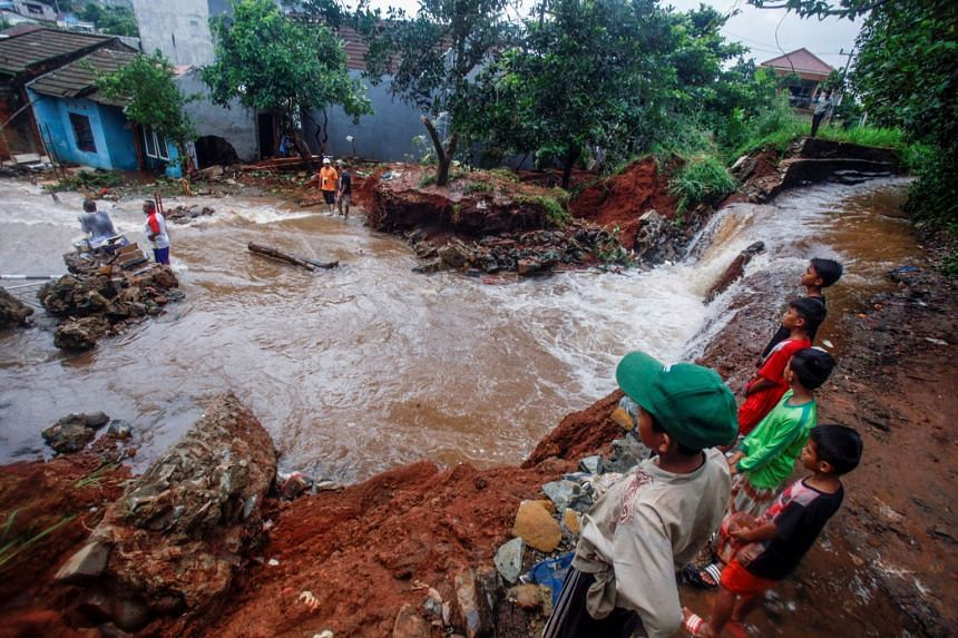 People gather around a dam which collapsed after heavy rain in West Java, on Jan 2, 2020.