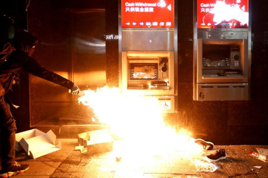 An anti-government protester feeds a fire by an HSBC ATM during an anti-government demonstration in Hong Kong on Jan 1, 2020.