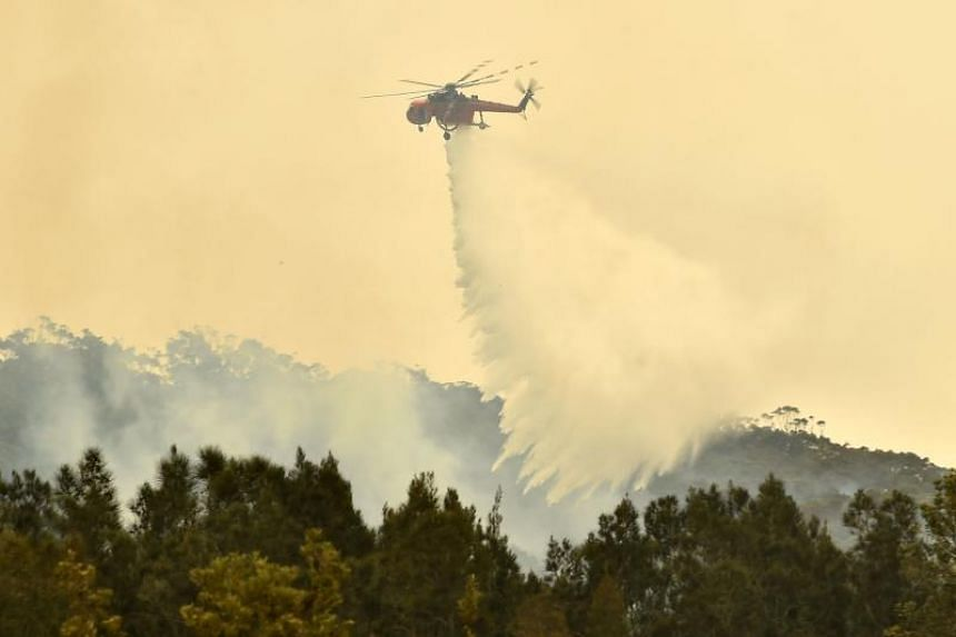 A helicopter drops water on a bush fire outside of Batemans Bay in New South Wales, Australia, on Jan 2, 2020.