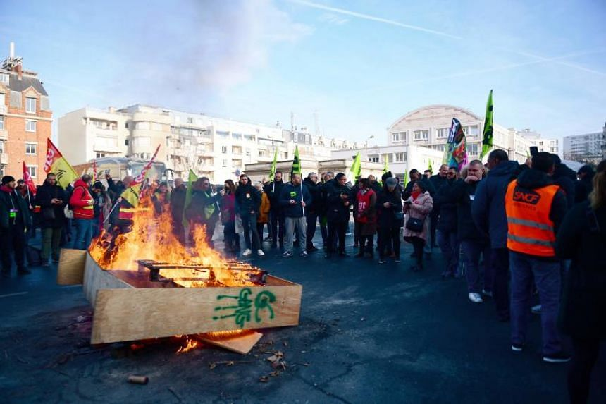 Members of unions gather around a fire at the Gare de Lyon train station in Paris, on Dec 31, 2019.