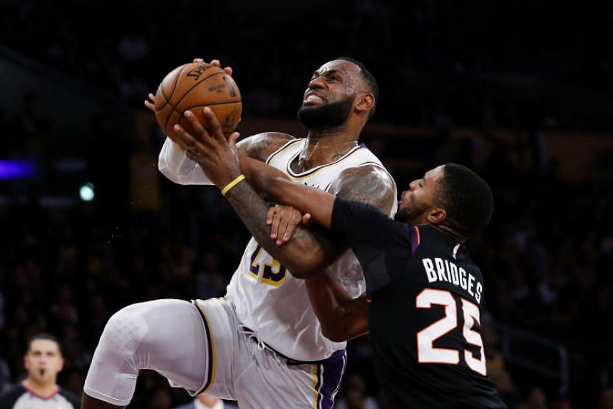 Los Angeles Lakers' LeBron James (left) is fouled by Phoenix Suns' Mikal Bridges during the second half on Jan 1, 2020.