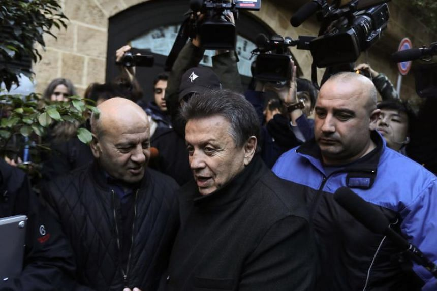 Lebanese lawyer Sakhr al-Hashem (centre) talks to journalists outside a house identified by court documents as belonging to former Nissan chief Carlos Ghosn in Beirut, on Jan 2, 2020.