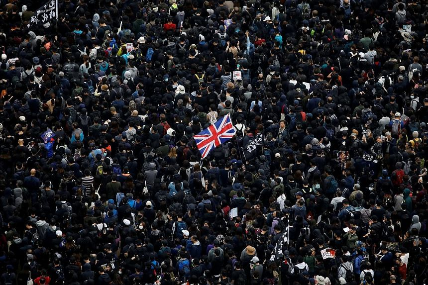 A protester holding up a British flag during an anti-government rally in Hong Kong on Wednesday. Sources said China has temporarily suspended the Shanghai-London Stock Connect scheme because of political tensions with Britain, with two of them highli