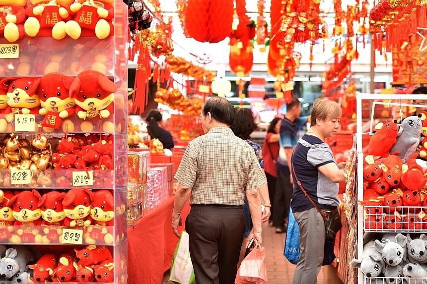 Shoppers browsing at a fair selling Chinese New Year decorations and mouse plush toys for the Year of the Rat in Ang Mo Kio on Tuesday. ST PHOTO: KELLY HUI A woman (above) posing for a photo with tangerines at a Chinese New Year goods stall and stude
