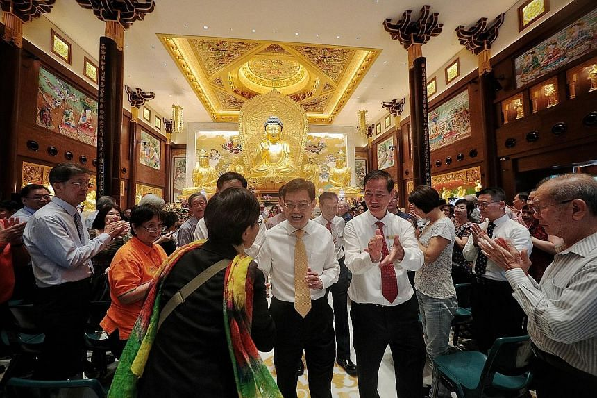Devotees (above) praying at a ceremony yesterday to open a new hall and consecrate a golden Buddha statue at the Singapore Buddhist Lodge (SBL) in Kim Yam Road. Deputy Prime Minister Heng Swee Keat (right), seen here with SBL president Tan Lee Huak,