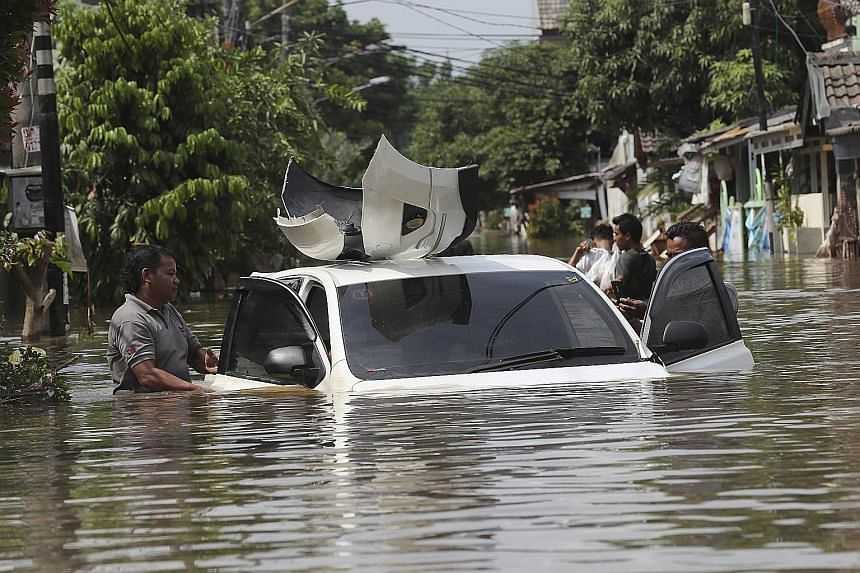 People wading through a flooded neighbourhood (top) in Tanggerang, on the outskirts of Jakarta, yesterday. The neighbourhood, like many in Jakarta and its surrounding areas, experienced severe flooding (above) after the heaviest downpour in a single