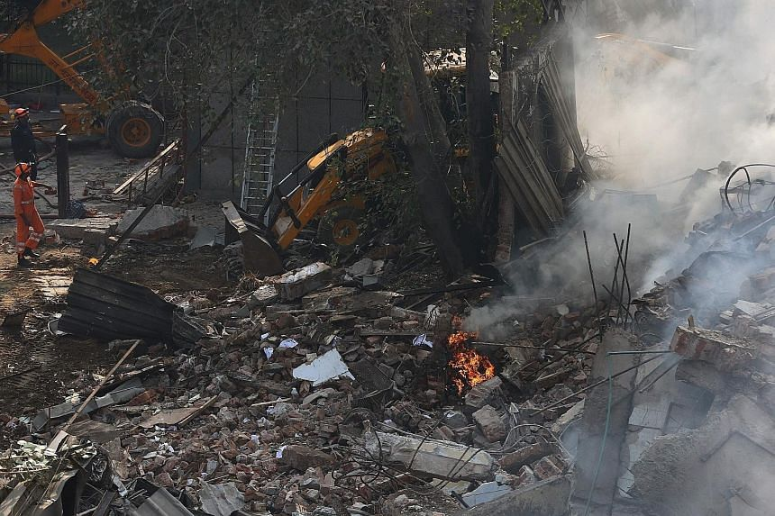 Rescue workers at the site of the fire in New Delhi, the third major blaze in the Indian capital in less than a month. The blaze was extinguished, but heavy smoke engulfed the rear portion of the factory building which collapsed. It contained inflamm