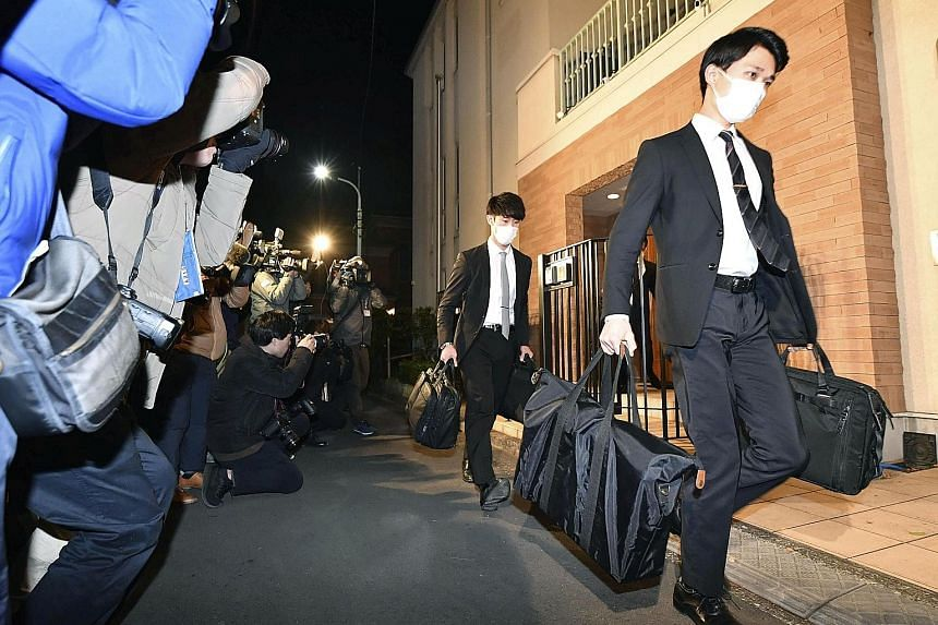 Officials from the Tokyo District Public Prosecutors Office carrying bags out after raiding the Tokyo residence of Carlos Ghosn as part of an investigation into his escape from Japan to Lebanon. NHK said the authorities are expected to analyse securi