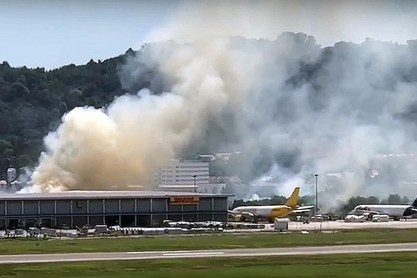 Thick, white smoke billowing from behind the cargo building opposite the runway of Penang airport on New Year's Day. The fire, caused by burning grass, was put out by the airport's firemen. PHOTO: THE STAR/ ASIA NEWS NETWORK