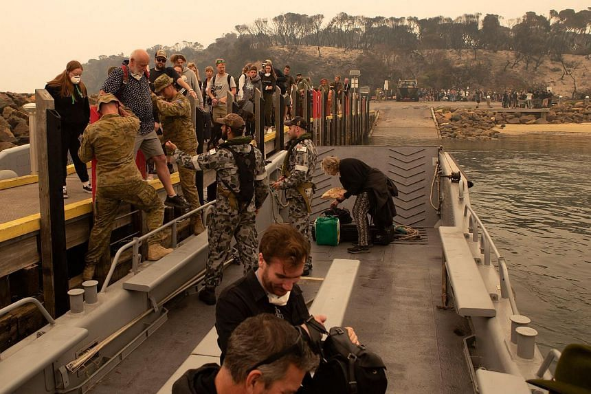 People being evacuated to the HMAS Choules during bush fire relief efforts in Mallacoota, Victoria, on Jan 3, 2020.