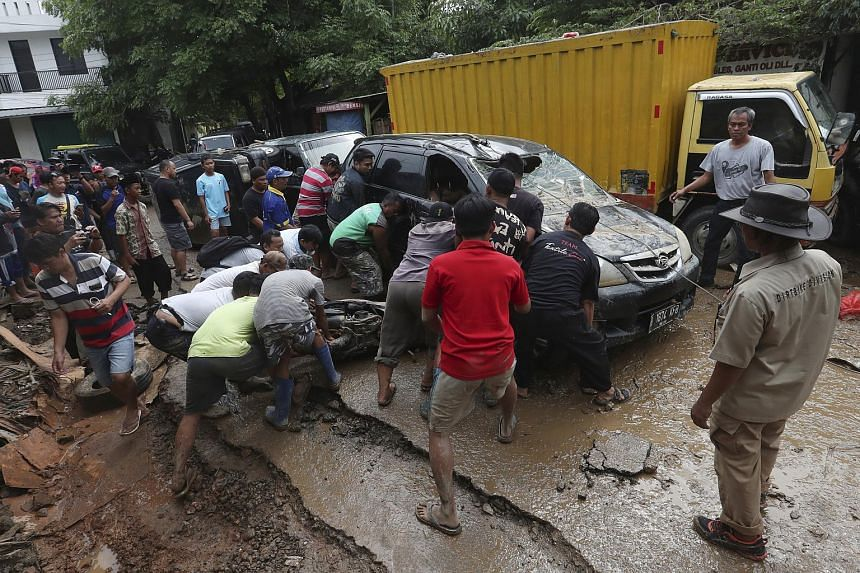 Residents move the wreckage of cars swept away by the floods in Bekasi, Indonesia, on Jan 3, 2020.