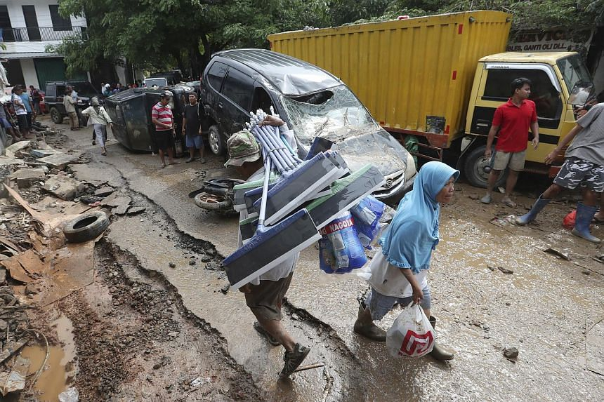 Residents walk past the wreckage of cars swept away by the floods in Bekasi, Indonesia, on Jan 3, 2020.