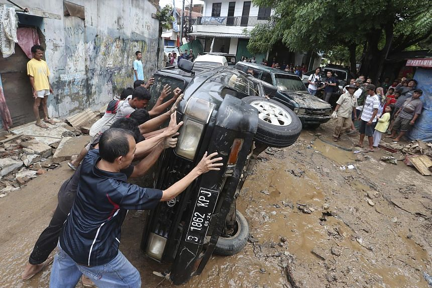 Residents move the wreckage of cars swept away by floods in Bekasi, Indonesia, on Jan 3, 2020.
