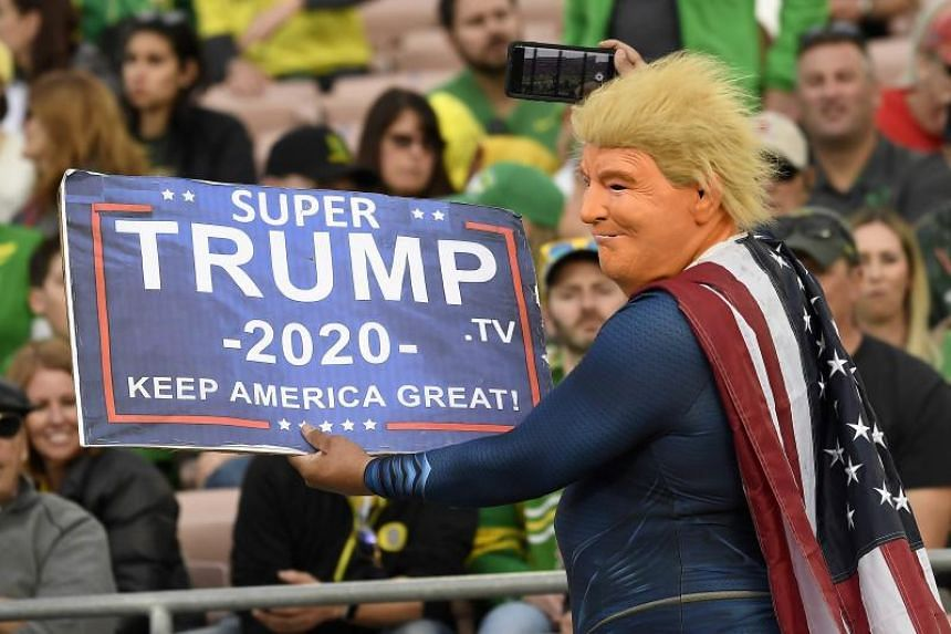 """A fan dressed as Super Trump holds up a sign that reads, """"Super Trump 2020 Keep America Great!"""" during the Rose Bowl game on Jan 1, 2020 in Pasadena, California."""