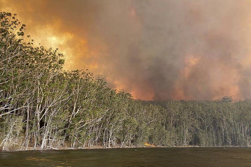 Smoke and wildfire rage behind Lake Conjola, Australia, on Jan 2, 2020.