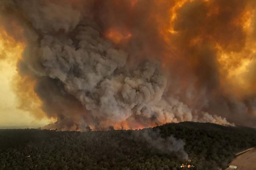 A photo from Dec 30, 2019, shows wildfires raging under plumes of smoke in Bairnsdale, Australia.