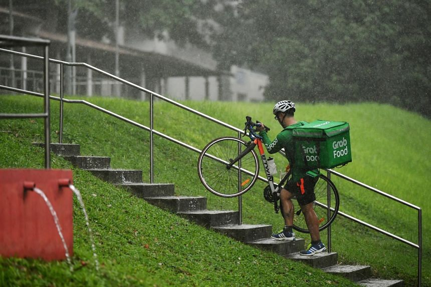 A GrabFood rider carrying his bicycle up the stairs in Bishan, on May 13, 2019.