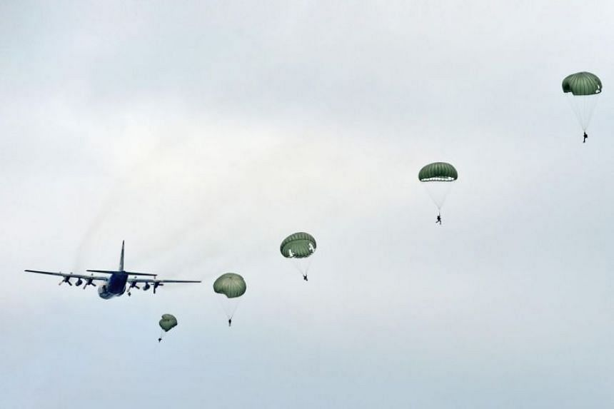 In a photo taken on May 14, 2013, a string of parachutes bloom behind the C-130 Hercules.