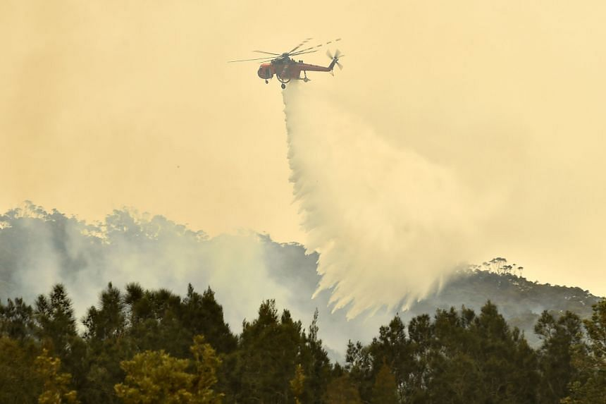 A helicopter drops water on a bushfire outside of Batemans Bay in New South Wales on Jan 2, 2020.