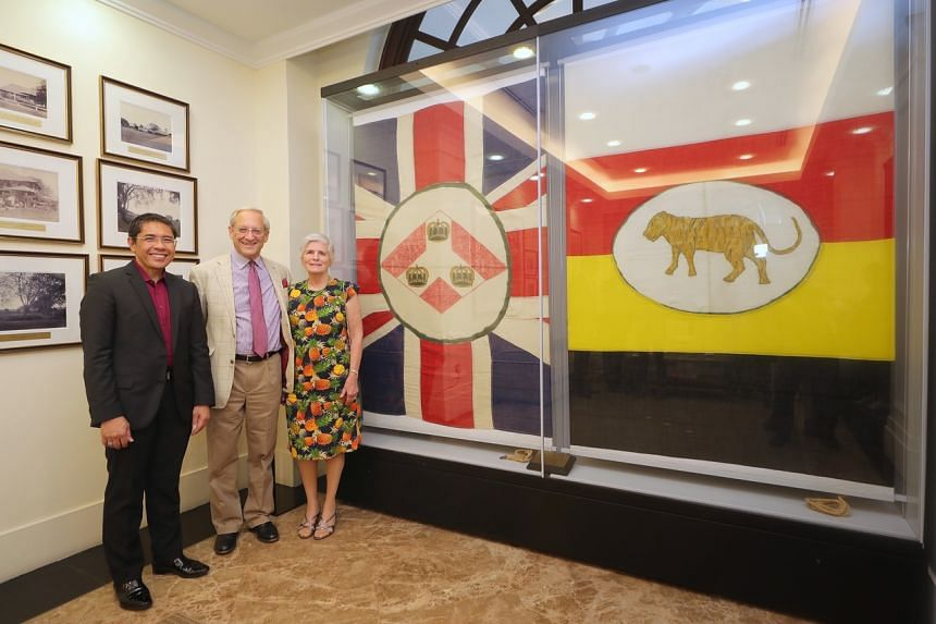 (From left) Senior Minister of State for Defence and Foreign Affairs Maliki Osman and the family of the late Lt-Col Geoffrey Sherman, son Nicholas Sherman and daughter-in-law Rosemary Sherman, viewing two flags in the Old Tanglin Officer's Mess at th