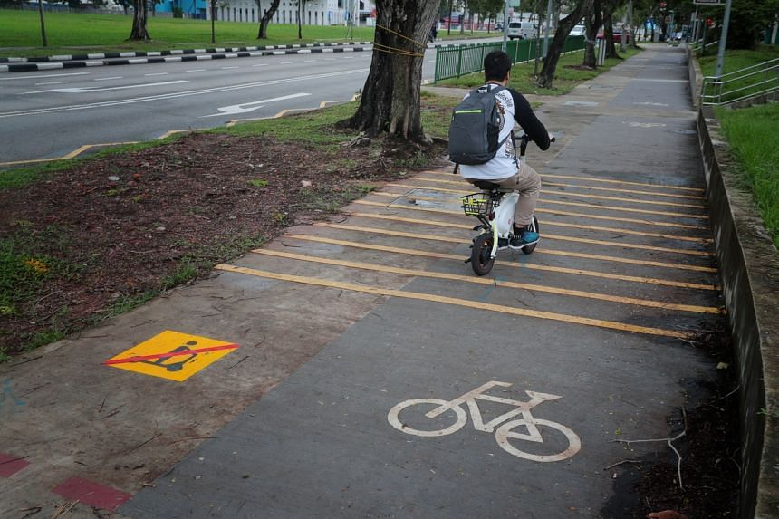 A man riding an electronic scooter crosses over from a footpath with a sign indicating the PMD ban on footpaths, to a cycling path, along Jurong East St 31, on Dec 17, 2019.