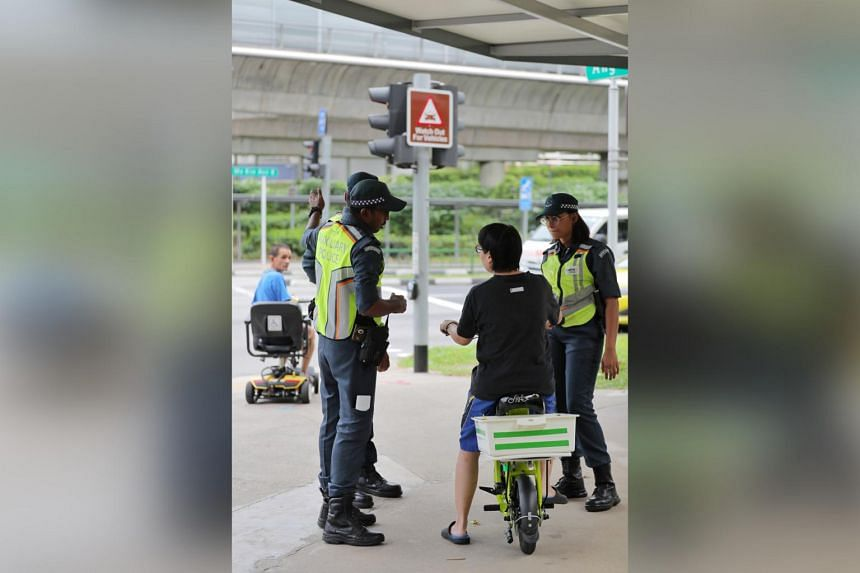 LTA enforcement officers and auxiliary police officers advising a PMD user on where he can ride his device at the junction near AMK Hub on Jan 2, 2020.