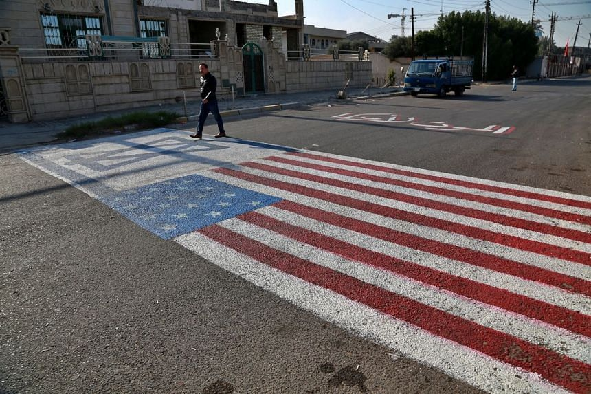 A man walks on the representations of the US and Israeli flags in Baghdad on Jan 3, 2020.