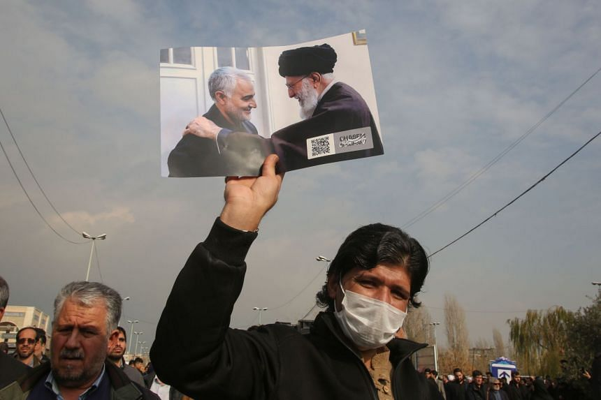 A man holds a picture of Iran's supreme leader Ayatollah Ali Khamenei with Iranian Revolutionary Guards Major-General Qasem Soleimani (left) during a demonstration in Teheran.