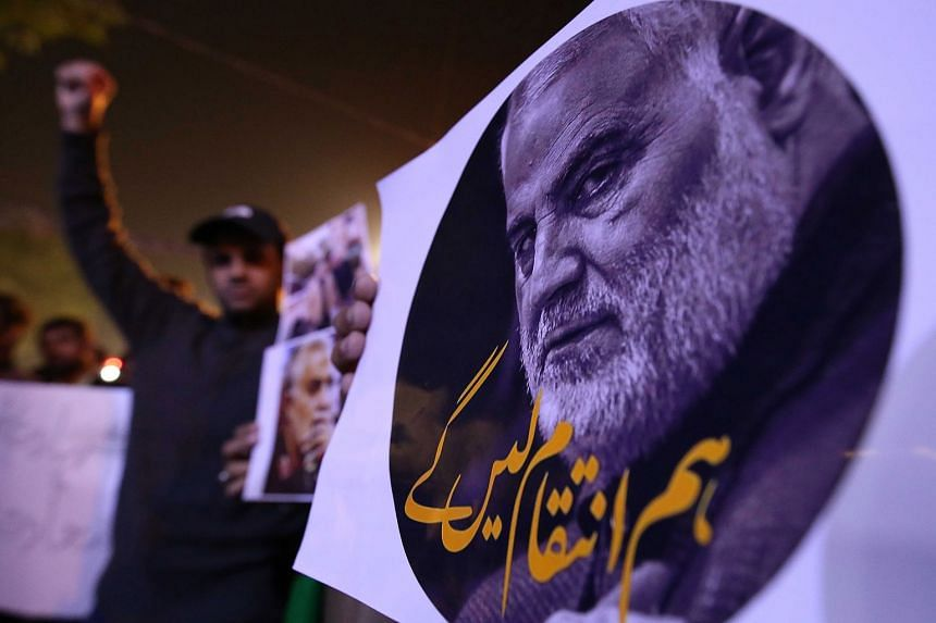 Pakistani Shi'ite Muslims hold pictures of General Qasem Soleimani during a protest in Karachi.