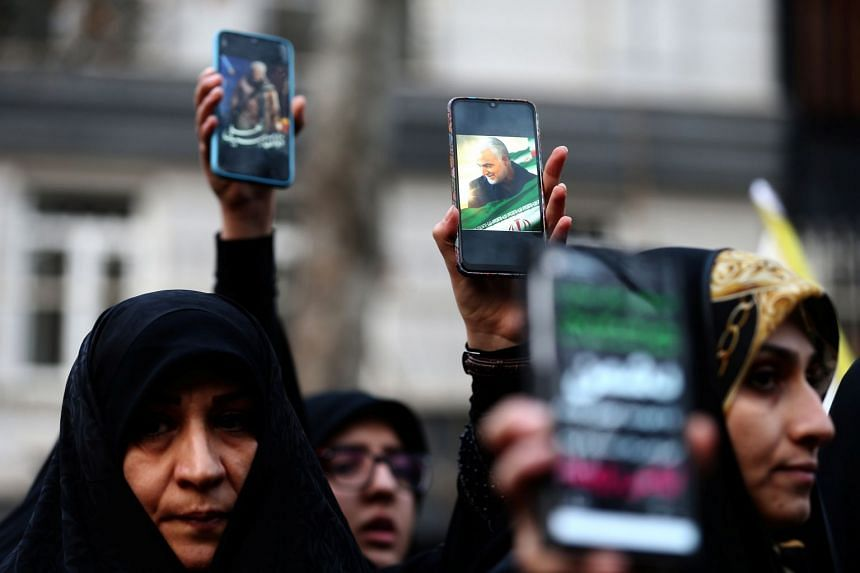 Iranian demonstrators hold up mobile phones showing pictures of Soleimani, during a protest in Teheran.