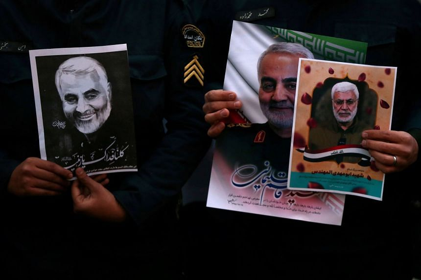Iranian guards hold pictures of Soleimani in front of the United Nations office in Teheran.