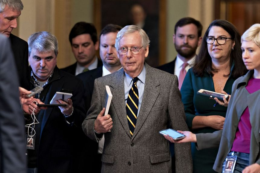 Senate Majority Leader Mitch McConnell (centre) walks to his office after speaking on the Senate floor at the US Capitol.