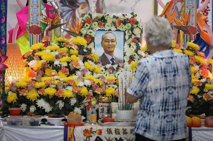 A visitor paying her respects to the late Mr Kee Kin Tiong at his wake yesterday.