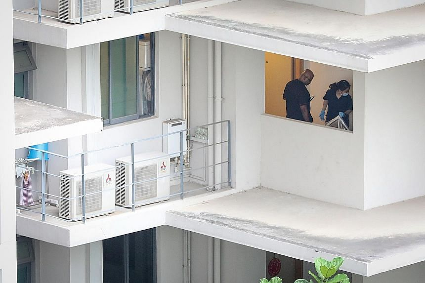Police investigators were seen in the third-floor unit at Esparina Residences where the 43-year-old woman was found dead yesterday.