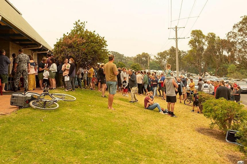 Top: People being evacuated from Mallacoota in Victoria state yesterday, after wildfires forced 4,000 residents and tourists to seek shelter on beaches. Above: Crowds lining up on Thursday to register for evacuation by HMAS Choules in Mallacoota, whe