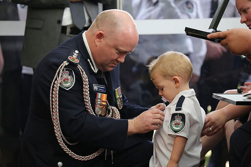 New South Wales' Rural Fire Service Commissioner Shane Fitzsimmons pinning a medal for bravery on 19-month-old Harvey Keaton's shirt during his father Geoffrey Keaton's funeral in Sydney on Thursday.
