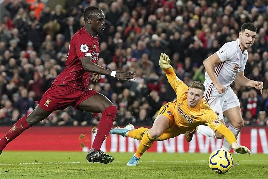 Sadio Mane scoring Liverpool's second goal during their EPL match against Sheffield United at Anfield on Thursday. Mohamed Salah was the other scorer in the 2-0 win that took Liverpool's lead over second-placed Leicester to 13 points, with a game in hand.