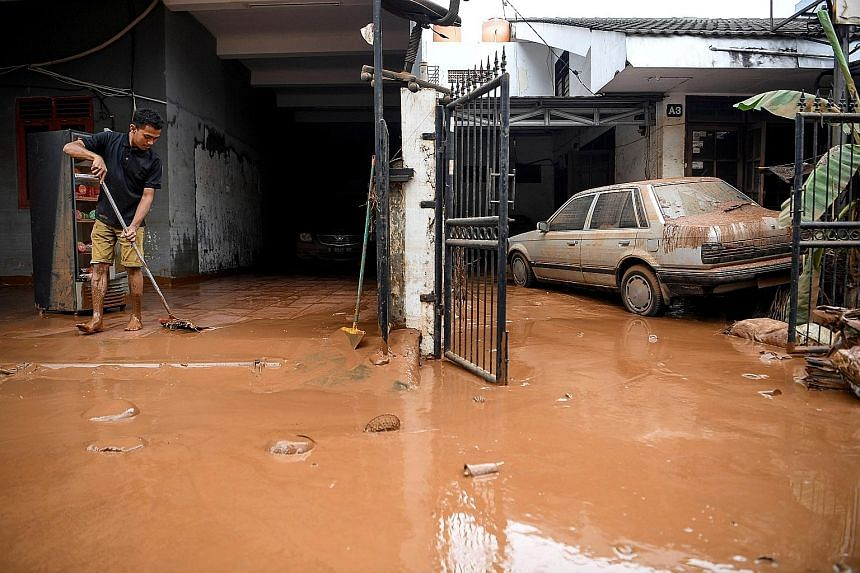 A man sweeping away the mud left by the floods yesterday in a residential area in Bintaro, Jakarta. Emergency response staff have started clearing some access roads to make way for residents to return to their homes. PHOTO: REUTERS Residents cleaning