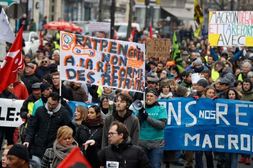 "A protester holds a banner reading ""RATP (Paris' public transport operator) on strike. No to the pension reform"" during a march in Paris, on Jan 4, 2020."