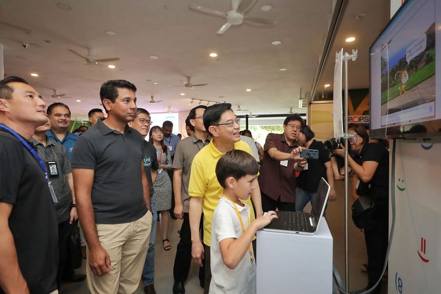 (From left) IMDA Chief Executive Tan Kiat How, Google vice-president Caesar Sengupta and Deputy Prime Minister Heng Swee Keat view Aiden McEwan's Five Question Quiz project at the Code in the Community graduation ceremony at Our Tampines Hub on Jan