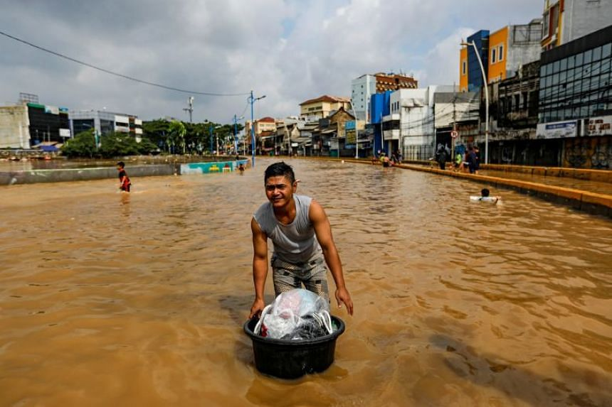 A man carrying his belongings across floodwaters at the Jatinegara area after heavy rain in Jakarta on Jan 2, 2020.